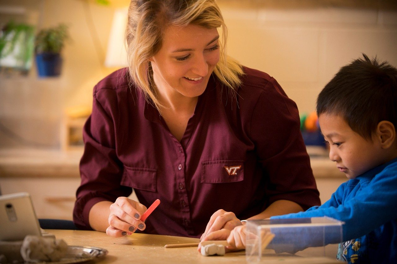 Virginia Tech alumna Emily Phillips works with a child